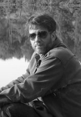 Black and White Photo of Bearded White Man in Sunglasses Sitting By A Still Pond