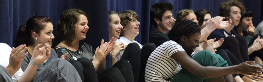 Several Artstrek Students Laugh And Applaud For Something They Are Watching Out of Frame