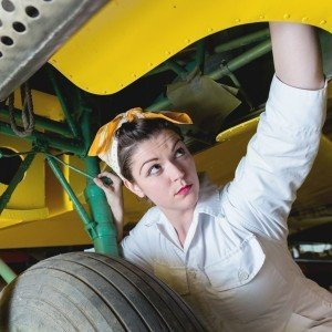 White Woman Working on Mechanical Devices On Underside of Yellow Plane