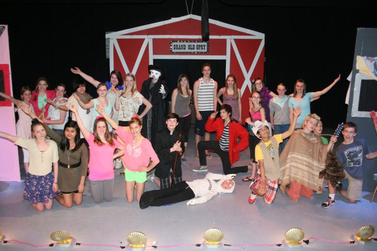 """Two Dozen Young Performers Posing In Front of Red Barn on Stage with """"Grand Old Opry"""" Sign"""