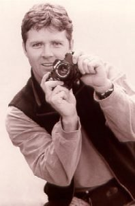 White Man Leaning to His Right and Holding Camera
