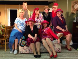 Middle Aged Cast Posing for Photo Sitting on Floral Love Seat Some Are Wearing Crimson Hats