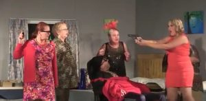 Woman in Red Dress Pointing Gun at Other Women While Man is Tied to A Chair