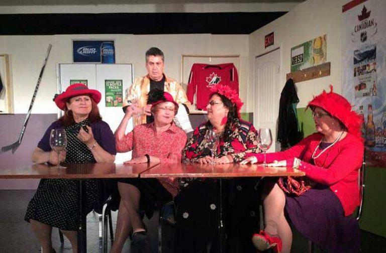 Four Older Women Wearing Crimson Caps Sitting at Table