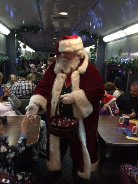the polar express train ride mossleigh alberta santa giving the first gift of christmas a silver sleigh bell