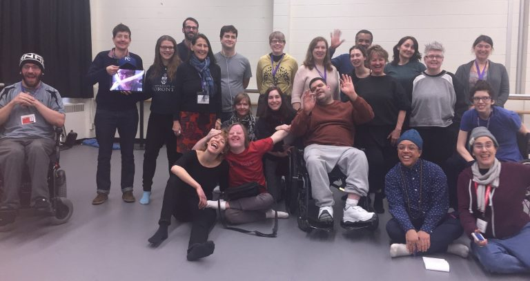 Two Dozen DisArts Group Workshops by Request Participants Pose Smile and Wave for the Camera. Some Stand, Some Sit on Ground, and Some Sit in Wheelchairs.