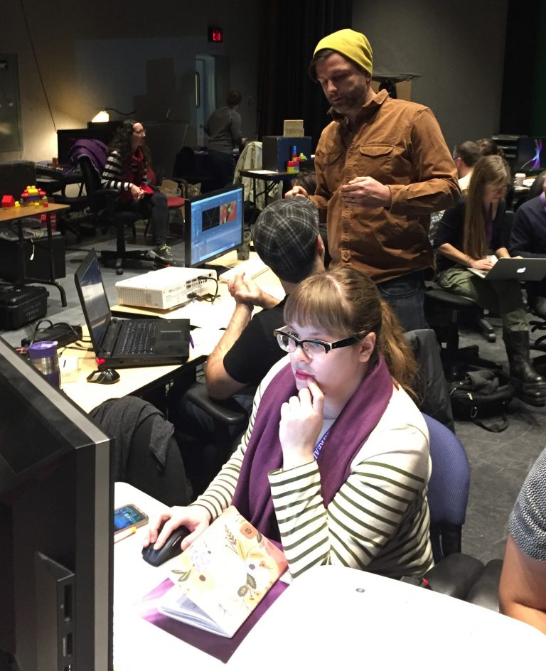 White Woman with Brown Hair, Glasses, and Purple Scarf Sits At Computer Thinking Deeply With Hand Resting By Mouth