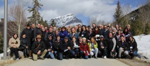 A Few Dozen Attendees of The Rocky Mountain Series's Community Theatre Summit Pose For a Photograph Outside in Banff With Mountains and Trees Behind Them