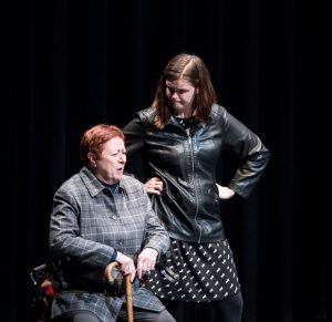 White Woman in Jean Jacket Looking on Older White Woman with Red Hair and Cane Sitting on Walker