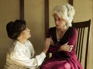 Brunette White Woman Comforting Wealthier White Woman With White Hair Both in Period Garb