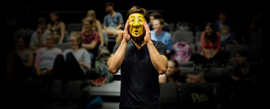 Man Wearing Yellow Theatre Mask Standing In Front of a Group of Other Students in Chairs