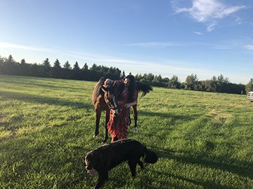 Tai Amy Grauman in a field with a horse and a dog.