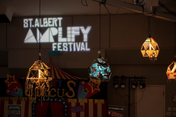 Image of decorated hanging lights. Text St. Albert Amplify Festival