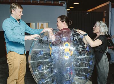 "POV Directors Jeremy Park & Michelle Brandenburg outfit ensemble member Jennifer Stewart in her ""Charlotte Bubble"" Bubble in rehearsal for Most Imaginary Worlds"