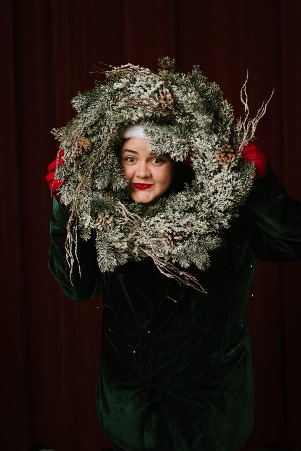 Image of actor peeking through a holiday wreath.
