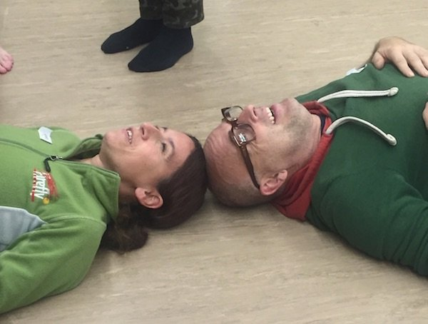 White Man and White Woman Lay Face-up On Floor at Workshops by Request Rocky Mountain Series Workshop, Smiling, With Tops of Heads Touching