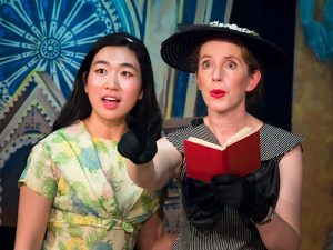 East Asian Women in Yellow Floral Dress and White Woman In Black and White Dress Sing On Stage While White Women Holds Red Book