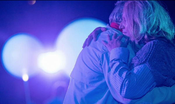 Two people hugging. Bright lights in the background.