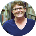 Smiling Middle-Aged White Woman With Short Light Brown Hair and Glasses Standing By Bookshelves