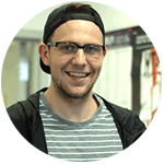 Smiling White Man With Backwards Cap and Glasses