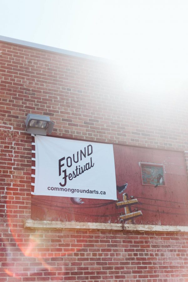 Brick wall with Found Festival sign on it. Website: commongroundarts.ca