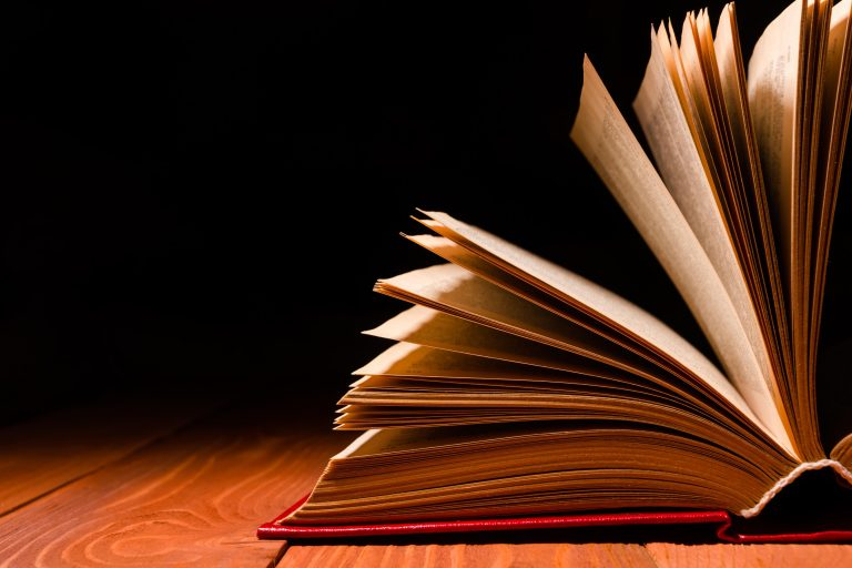 An Open Book With Splayed Pages Sitting On a Wooden Table