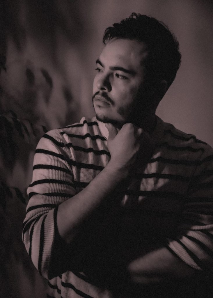Andrés is light skinned, and has a trimmed beard and short hair. They are wearing a white and black striped sweater and they stand looking off pensively to the left side of the picture. They have a focused expression on their face and their arms are folded with one arm crossing their chest. The picture has a rose grey filter.