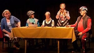 Five Senior Actors Sit or Stand By Long Table With Yellow Tablecloth Some Wear Bike Helmets