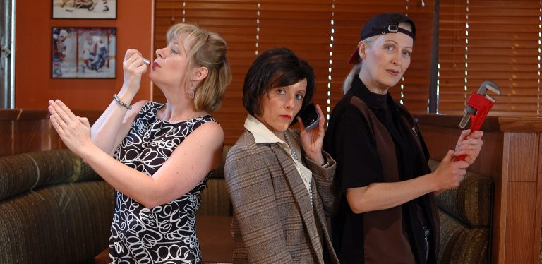 Three Women Pose One Applies Lipstick One On Phone One With Backwards Baseball Cap and Red Industrial Wrench