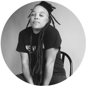 Black Human with Cascading Dreadlocks Sitting on Chair Looking At Camera