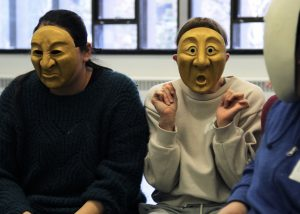Two Workshops By Request Participants Wearing Yellow Theatre Masks - One Mask Looks Grumpy One Looks Surprised