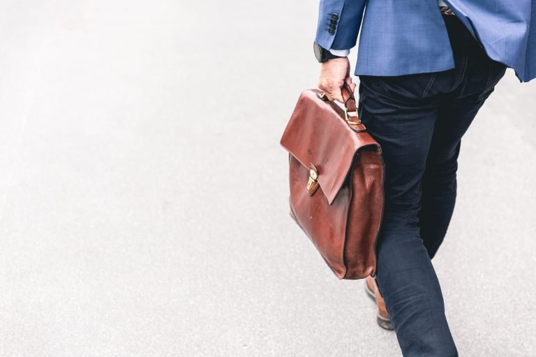 Lower-Half of Man in Dark Denim Walking on Concrete While Holding Leather Briefcase