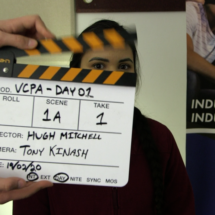 Human standing behind a film clapboard