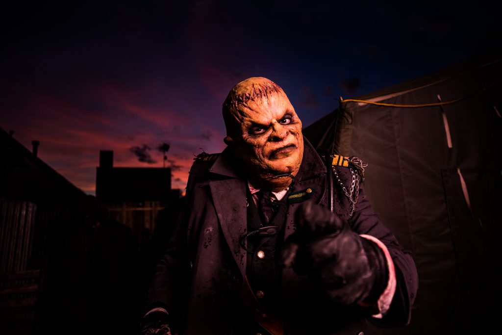 Scary Halloween creature against a dark sunset background.