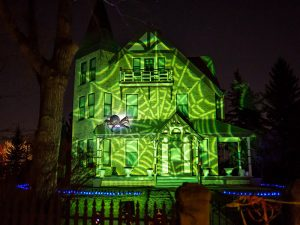 Image of an Prince House at Heritage Park lit with a green spiderweb across the front of the house