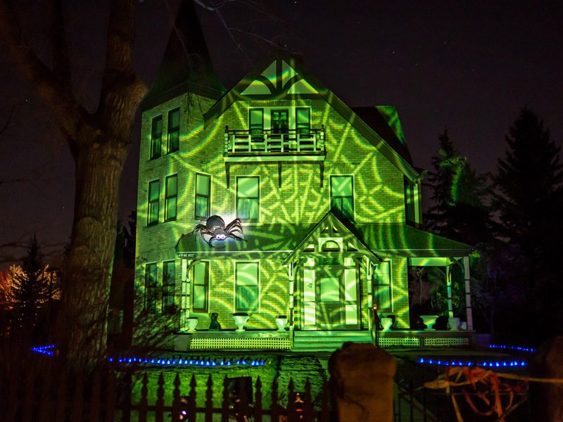 Image of an old house with a green lit spiderweb across the front of the house