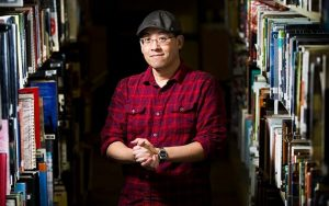 Marty Chan standing between stacks of books