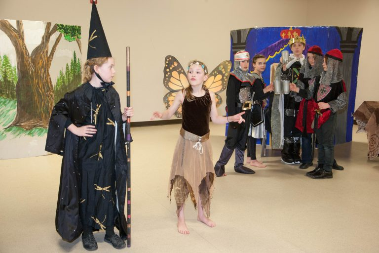 Youth performing a scene dressed in medieval costumes