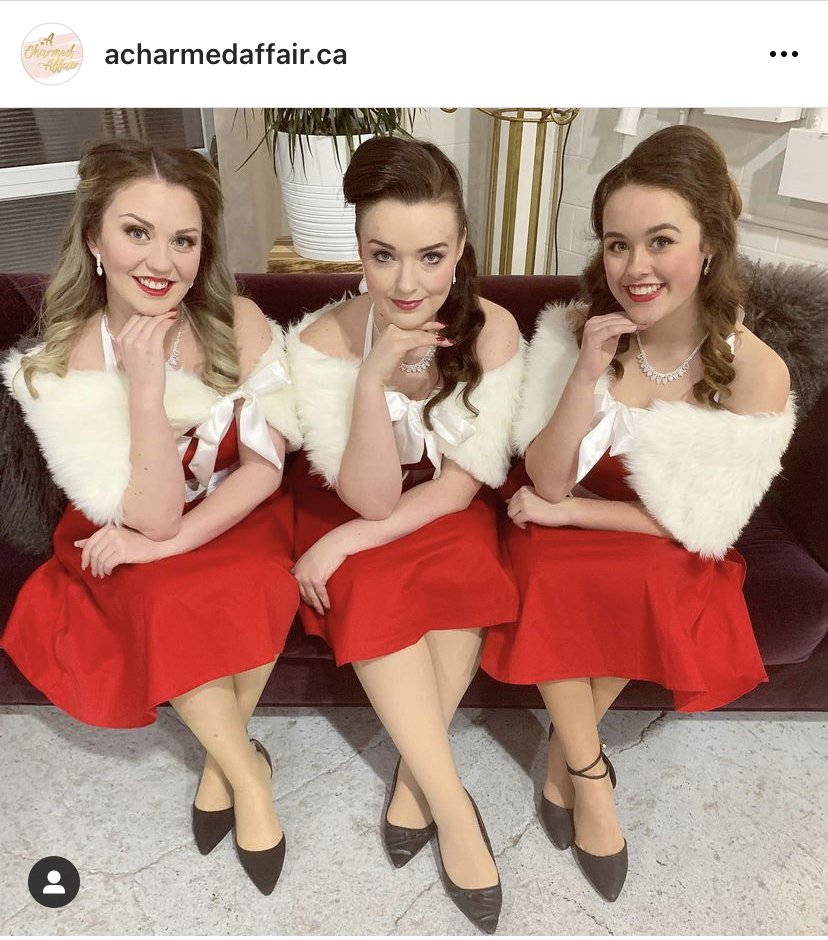 Three female-presenting people dressed in 50's style dresses