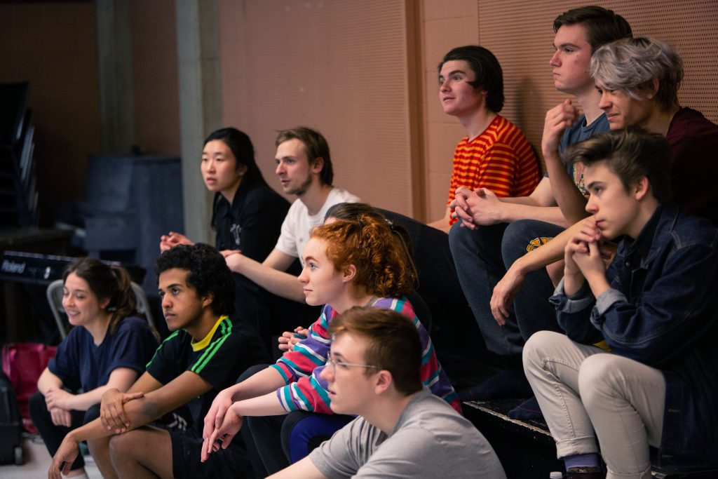 Group of young people watching a theatre performance