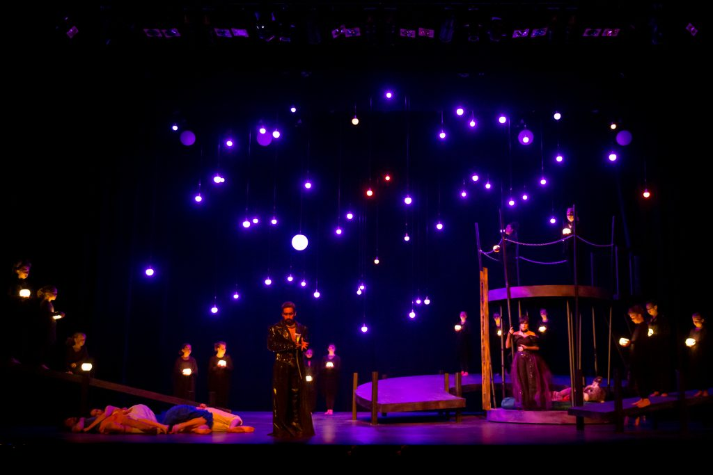 Image of a dimly lit stage with star-like lights in the background. Two actors are on stage.