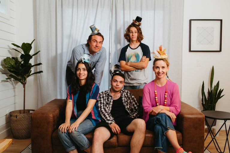 Five people in a living room setting posing with tiny party hats.